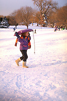 Girl age 6 carrying saucer back up hill for another winter run. Town and Country golf course St Paul  Minnesota USA