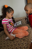 MR / Schenectady, New York. Young child (girl, 6, Puerto Rican American) uses iPad to read eBook / app at home as brother (boy, 3, Puerto Rican American) looks on. ID: Con7, Mel18 . ©Ellen B. Senisi