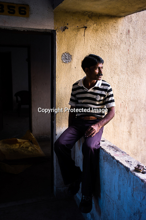 42 year old Ashok Paswan poses for a photo outside the two alloted units in Belgharia township outside of Dhanbad in Jharkhand, India.  Families from various villages with underground fires have been rehabilitated in Belgharia township. Photo: Sanjit Das/Panos