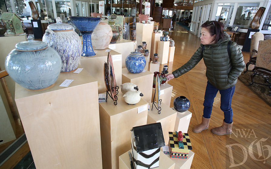 NWA Democrat-Gazette/DAVID GOTTSCHALK Kathy Pare leans in to take a look Wednesday, January 9, 2019, at handcrafted pottery created by members of the Boston Mountain Potters Association at the Bank of Fayetteville on the square in Fayetteville. The pottery, all available for purchase, will be up through the month of January.