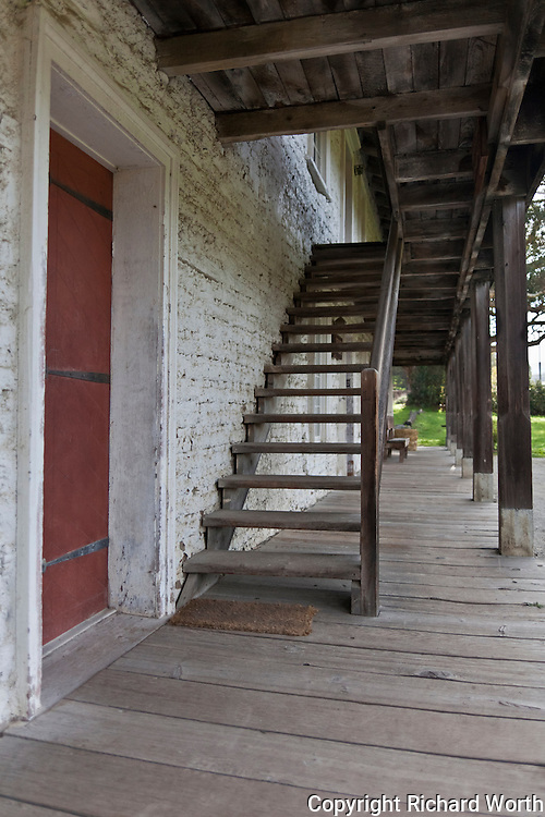 Next to a weathered red door, wooden stairs lead to the second floor balcony of the Sanchez Adobe in Pacifica, California.