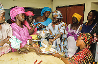 Woman's group preparing and cooking in a solar oven self-made mangos and banana marmalade for the sell at the market