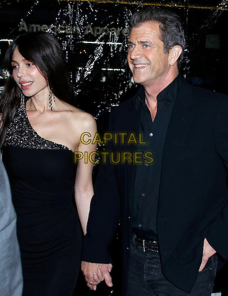 "OKSANA GRIGORIEVA & MEL GIBSON.he Los Angeles premiere of ""Edge of Darkness"" at Grauman's Chinese Theatre in Hollywood, California, USA. .January 26th, 2010 .half length maxi dress suit jacket  holding hands black shirt one shoulder couple beaded jewel encrusted embellished .CAP/ADM/MJ.©Michael Jade/AdMedia/Capital Pictures."