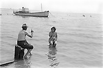 """Southend-on-Sea, Essex. 1969<br /> Ignoring the incoming tide a couple discuss some of the finer points of life. Sir John Betjeman once said that, """"The Pier is Southend, Southend is the Pier"""". It's the longest pier in the world extending 1.34 miles into the Thames Estuary."""