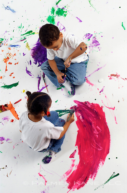 Little boy and girl working on a large painting on the floor in classroom