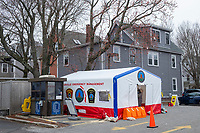 The intake tent stands near houses as COVID-19 drive-through testing takes place in a parking lot near the Cambridge Health Alliance Women's Health Hospital in Somerville, Massachusetts, on Mon., March 23, 2020. Patients could make appointments to drive through the parking lot to get tested for the virus during the ongoing Coronavirus (COVID-19) global pandemic. This location is one of a handful of such testing facilities that have opened in the Boston area in the past week.