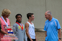 Dale Shepherd speaks with Varsity Boys winner Evan Schulte, while second and third placers Dorrian Gordon and Dylan Quisenberry look on.