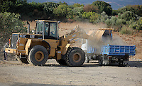 Pictured: A digger loads a tipper lorry with soil from the second site to be transported to the farmhouse so that specialist officers search through it in Kos, Greece. Monday 10 October 2016<br />