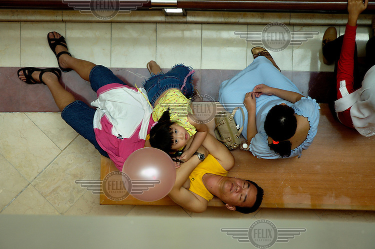 A father sleeping while a Chinese family group take a break in a shopping mall.