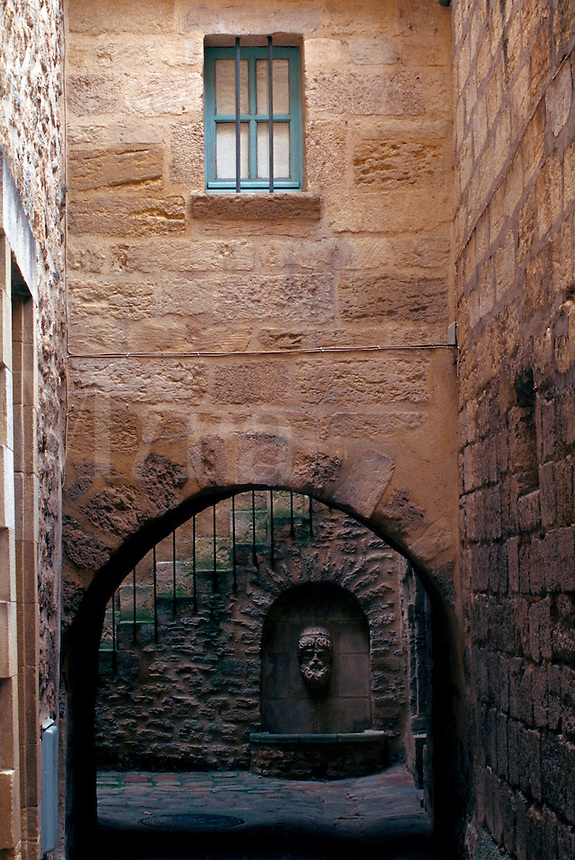 The interior of a courtyard with an ornate wall fountain as seen through a stone arch. France.