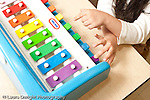 Education preschool 3-4 year olds closeup of girl's hands as she plays toy piano xylophone horizontal