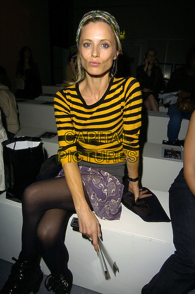 LAURA BAILEY.At the BIBA Spring/Summer 2007 Catwalk Show during London Fashion Week, BFc Tent, Natural Hitsory Museum, London, England, September 19th 2006..full length yellow and black striped jumper top stripes head scarf hair purple patterned print skirt black tights ankle booots sitting funny face lips pouting.Ref: CAN.www.capitalpictures.com.sales@capitalpictures.com.©Can Nguyen/Capital Pictures