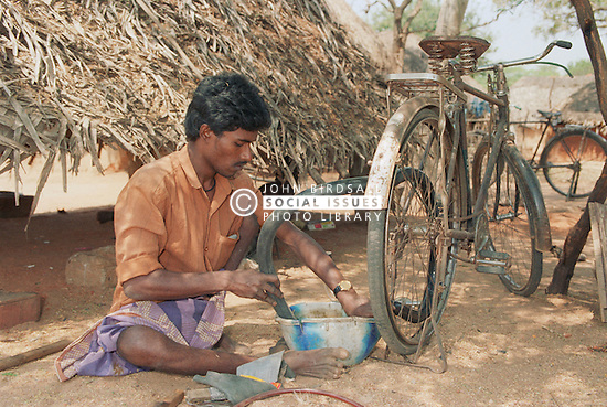 Indian man affected by polio; secretary of selfhelp group supported by charity ADD India; mending punctured bicycle tyre at cycle repair workshop,