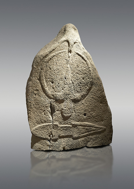 Late European Neolithic prehistoric Menhir standing stone with carvings on its face side. The representation of a stylalised male figure starts at the top with a long nose from which 2 eyebrows arch around the top of the stone. below this is a carving of a falling figure with head at the bottom and 2 curved arms encircling a body above. at the bottom is a carving of a dagger running horizontally across the menhir.  From Barrili I site, Laconi. Menhir Museum, Museo della Statuaria Prehistorica in Sardegna, Museum of Prehoistoric Sardinian Statues, Palazzo Aymerich, Laconi, Sardinia, Italy. Grey background.