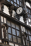 Old Tudor building facade with clock and statues of bishops and horrific faces, Winchester, England