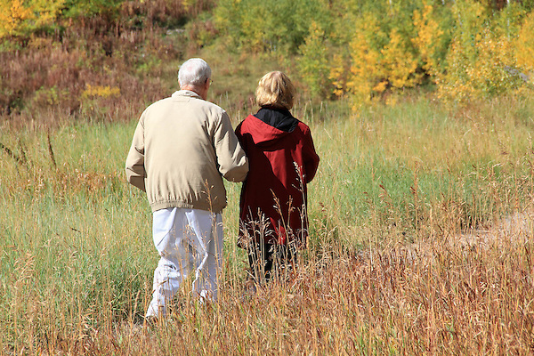 Elderly Caucasian man being helpd by middle aged woman, walking along the foothills near Boulder, Colorado, USA