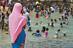 Africa, Afrika, Senegal, 17-09-2011, Dakar, Dakkar, Voor de kust van Dakar ligt het voormalige slaveneiland Isle de Goré. ( Goeree, uit het Nederlands) Tijdens de slavenhandel geregeerd door Nederlanders, en later over genomen door de Fransen.. Ook dit eiland staat op de UNESCO wereld erfgoed lijst. Een moslim meisje kijkt toe hoe andere inwoners zwemmen.. foto: michael Kooren/HH