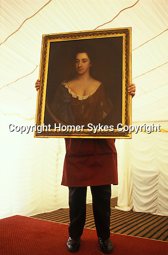 Newnham, Northamptonshire, England. A country house auction is conducted by the London auctioneers Christies at Newnham Hall. A  porter holds up a three quarter oil portrait so that the sale goers can see more clearly what they are bidding for. A marquee has been set up in the grounds and is where the auction takes place.
