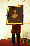 Newnham, Northamptonshire, England. A country house auction is conducted by the London auctioneers Christies at Newnham Hall. A  porter holds up a three quarter oil portrait of Miss Temperance Gell, so that the sale goers can see more clearly what they are bidding for. A marquee has been set up in the grounds and is where the auction takes place. 1994. 1990s UK