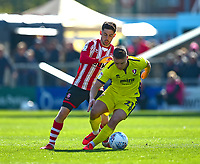 Lincoln City's Tom Pettbattles with  Cheltenham Town's Billy Waters<br /> <br /> Photographer Andrew Vaughan/CameraSport<br /> <br /> The EFL Sky Bet League Two - Lincoln City v Cheltenham Town - Saturday 13th April 2019 - Sincil Bank - Lincoln<br /> <br /> World Copyright © 2019 CameraSport. All rights reserved. 43 Linden Ave. Countesthorpe. Leicester. England. LE8 5PG - Tel: +44 (0) 116 277 4147 - admin@camerasport.com - www.camerasport.com