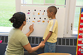 MR / Schenectady, NY. Zoller Elementary School (urban public school). Kindergarten classroom. Paraprofessional (Puerto Rican American) teaching Spanish language lesson to inattentive student (boy, 6, African American /  Puerto-Rican American) tries to get him to focus his attention. MR: Pac1, Cas12. ID: AM-gKw. © Ellen B. Senisi.