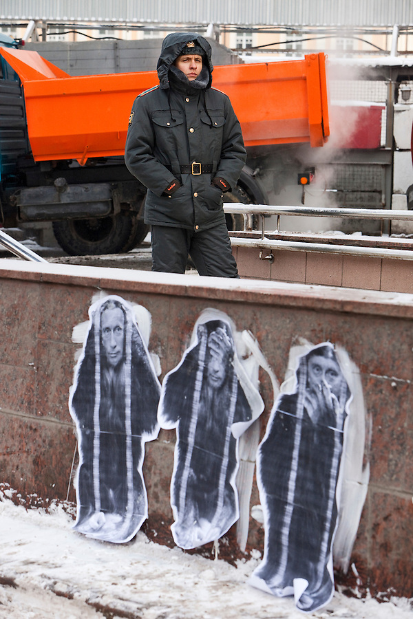 "Moscow, Russia, 04/02/2012..A Russian policeman standing behind graffiti depicting Prime Minister Vladimir Putin as the three monkeys ""Hear no evil, see no evil, speak no evil"" watches as tens of thousands of demonstrators march in central Moscow and protest against election fraud and Prime Minister Vladimir Putin in temperatures of -20 centigrade. Organisers claimed an attendance of 130,000 despite the bitter cold."