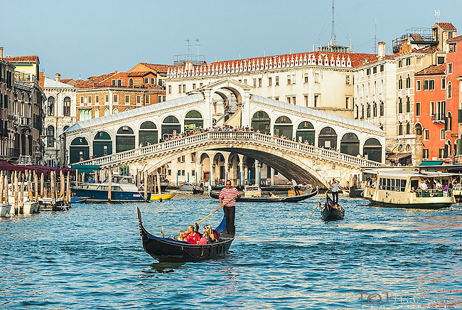 A family enjoy a gondola ride on the Grand Canal near the Rialto Bridge in Venice, Italy.