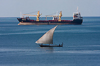 Zanzibar, Tanzania.  Cargo Freighter and Traditional Dhow Share the Harbor in Zanzibar.