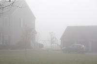 House, playground, car and garage shrouded in a foggy dawn