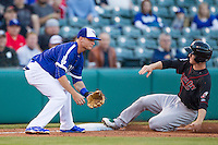 Oklahoma City Dodgers third baseman Buck Britton (4) waits for the ball as Nashville Sounds second baseman Joey Wendle (13) slides into third base at Chickasaw Bricktown Ballpark on April 15, 2015 in Oklahoma City, Oklahoma. Oklahoma City won 6-5. (William Purnell/Four Seam Images)