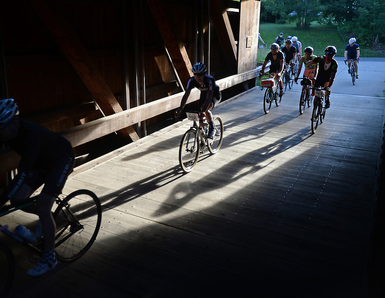 (Conway, MA, 08/22/15) Cyclists participating during the Deerfield Dirt Road Race pass through the Burkeville Covered Bridge over the Deerfield River in Conway, Mass., on Saturday, August 22, 2015. Photo by Christopher Evans