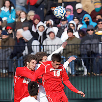 University of New Mexico forward Carson Baldinger (22), University of Connecticut defender Sean Weir (13), and University of New Mexico defender Ben McKendry (19) battle for head ball. .NCAA Tournament. With a goal in the second overtime, University of Connecticut (white) defeated University of New Mexico (red), 2-1, at Morrone Stadium at University of Connecticut on November 25, 2012.