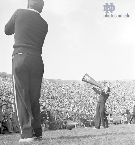 GMCJ 1/31:  Football Game Day - Notre Dame vs. Michigan State (MSU), 1950/1028.  Cheerleaders on the field with one yelling through a megaphone. This photo was published in the 1950 Scholastic Football Review. Image from the University of Notre Dame Archives.