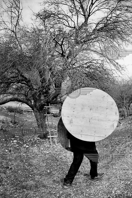 A man carries his household's tables to a funeral feast..