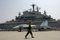 A man with camouflage coat walks past Soviet aircraft carrier Kiev and an air fighter in a military-theme park in Tianjin, China..19 Aug 2007
