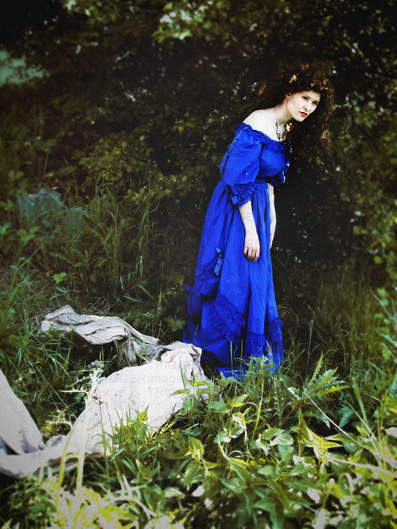 A woman in a blue vintage gown, standing among trees and plants in  a wild garden, with a long grey veil laying behind her.