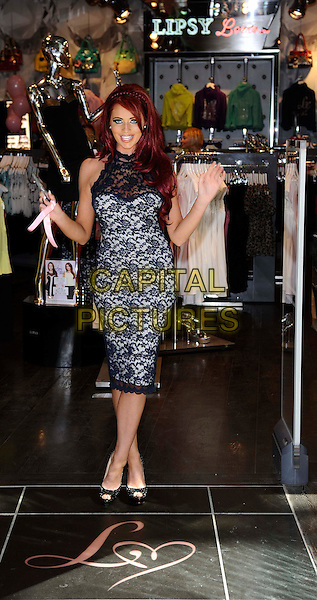 Amy Childs.Launches her new collection of clothes at Lipsy, Bluewater Shopping Centre. Kent, England, UK, May 25th 2012..full length navy blue lace sheer high neck dress black peep toe shoes scissors .CAP/DH.©David Hitchens/Capital Pictures.