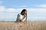 A young Native American Indian Woman sitting in the grasses of South Dakota