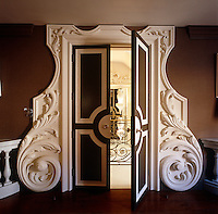 A double door within an ornately carved frame opens from the drawing room to the staircase landing