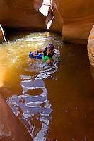 Man swimming across pool in narrow canyon.  Canyoneering, Fry Canyon, Utah