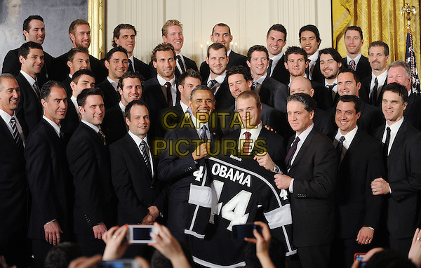 United States President Barack Obama poses with the Major League Soccer champion LA Galaxy to the White House to honor their 2012 championship seasons in a ceremony in the East Room of the White House March 26, 2013 in Washington, DC.  .half length black suit top smiling posing .CAP/ADM/CNP/OD.©Olivier Douliery/CNP/AdMedia/Capital Pictures.