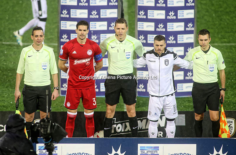 Pictured: Match referee Alexandros Aretopoulos (C) with officials and team captains before the game was abandoned at Toumba Stadium in Thessaloniki, Greece. Sunday 25 February 2018<br /> Re: Sunday's Greek Super League derby between PAOK Thessaloniki and Olympiakos was called off after Olympiakos' manager Oscar Garcia was struck in the face by an object believed to be a till machine paper roll, thrown by a spectator minutes before kick-off.<br /> Garcia left Toumba Stadium for a local hospital to seek treatment for a bloodied lip.<br /> The incident prompted the Olympiakos team to leave the pitch in protest before riots erupted outside the ground.<br /> Angry PAOK fans leaving the stadium then clashed with police who used tear gas to quell the violence.