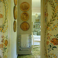 A glimpse into the bathroom from the landing past walls papered in a floral pattern