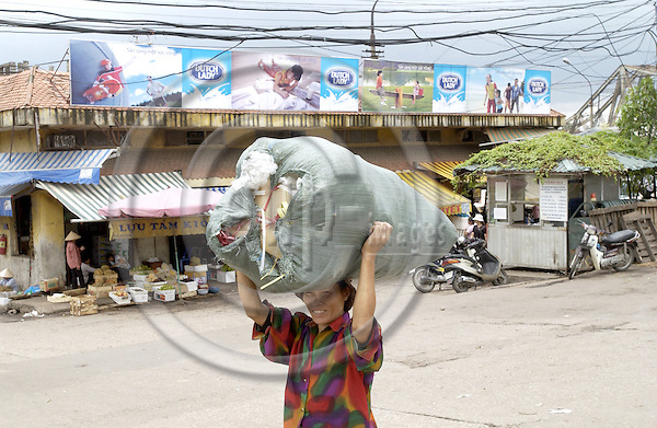 Hanoi-Vietnam, Ha Noi - Viet Nam - 24 July 2005---Woman carrying goods on her head from/to a market, western-style advertisement for diary products 'Dutch Lady' in the back--- transport, people, labour---Photo: Horst Wagner/eup-images
