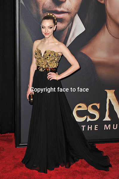 """Amanda Seyfried (wore a gold sequined heart shape bustier gown. Her long flowy black skirt was accentuated at the waist with a tortoise color wide ban belt. Other accessories includes an Alexander McQueen black satin skull clutch, and Harry Winston jewels) at the premiere of """"Les Miserables"""", New York, 10.12.2012...Credit: StarMaxInc/face to face..- Spain, Hungary, Bulgaria, Croatia, Russia, Romania and Moldavia, Slovakia, Slovenia, Bosnia & Herzegowina, Serbia, Ukraine and Belaurus, Lithuania, Latvia and Estonia, Australia, Taiwan, Singapore, China, Malaysia and Thailand rights only -"""