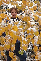 Woman standing among snow covered leaves