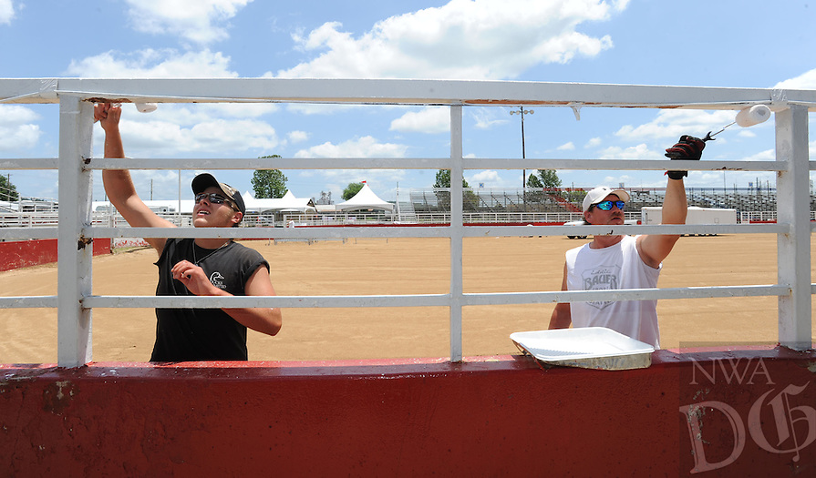 NWA Media/ANDY SHUPE - Workers Corbin Hanning of Springdale, left, and Ken Evans of Fayetteville paint the railing around Parsons Stadium Friday, June 20, 2014, in Springdale in preparation for the Rodeo of the Ozarks Western Days which is set for today. The event begins at 4 p.m. and features barbecue tasting at 5 p.m. and music from bands Alaska and Madi from 6 to 7:30 p.m. and Backroad Anthem from 8 to 10:30 p.m.
