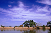 Pantanal, Mato Grosso, Brazil. Afternoon sky with river and river bank vegetation.