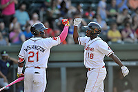 First baseman Josh Ockimey (18) of the Greenville Drive is congratulated by Kyri Washington after hitting a home run in a game against the Columbia Fireflies on Sunday, May 8, 2016, at Fluor Field at the West End in Greenville, South Carolina. Greenville won, 5-4. (Tom Priddy/Four Seam Images)
