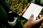 Anti-poaching snare removal team member, Godfrey Nyesiga, with notes of animal sign and illegal activities within the protected area, Kibale National Park, western Uganda